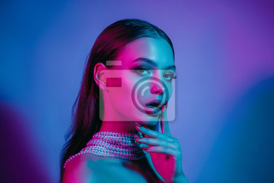 Plakat High fashion model in colorful bright neon lights posing at studio. Portrait of beautiful girl with trendy glowing make-up. Art design vivid style.
