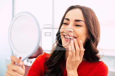 Plakat Honed to perfection. Fabulous woman clothed in red sweater, with curly long hair and elegant hands is holding a mirror for looking through the final work of dental doctor.