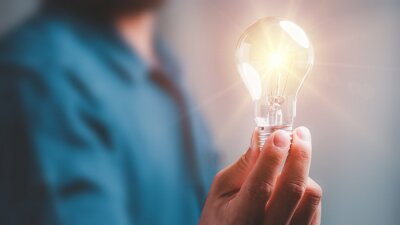 Plakat Idea innovation and inspiration concept.Hand of man holding illuminated light bulb, concept creativity with bulbs that shine glitter.Inspiration of ideas for sustainable business development.