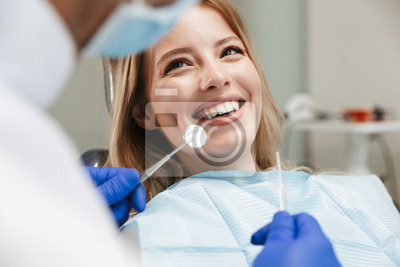Plakat Image of pretty woman sitting in dental chair while professional doctor fixing her teeth