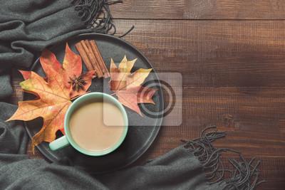 Plakat Jesieni wciąż życie z filiżanką kawy, kolorowi susi liście grżą szalika na drewnianej desce. Skopiuj miejsce. Widok z góry.