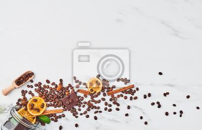 Plakat Kawa w szklanym słoju z fasolą, czekoladą, suszonymi pomarańczami, anyżem i cynamonem na białym tle z marmuru. Koncepcja kawy z różnymi przyprawami rozlewa się ze szklanego słoika. Skopiuj miejsce na
