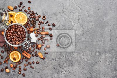 Plakat Kawa w szklanym słoju z fasolą, czekoladą, suszonymi pomarańczami, anyżem i cynamonem na szarym tle betonu. Koncepcja kawy z różnymi przyprawami. Widok z góry z miejsca kopiowania tekstu.