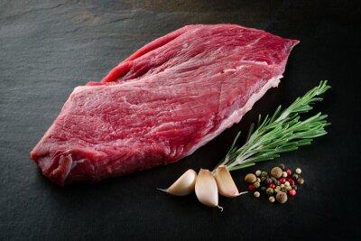 Plakat Kawałek surowego mięsa wołowego steku z przypraw na ciemnym tle