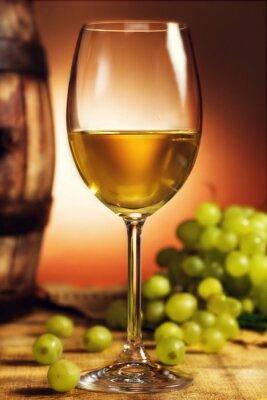 Plakat Kieliszek białego wina przed zielonych winogron i starej beczki