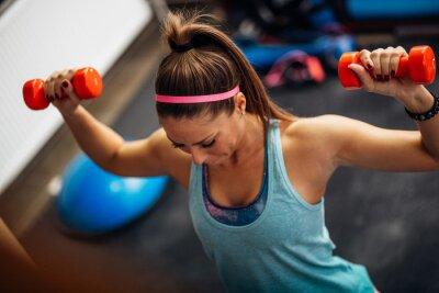 Plakat Kobieta podnoszenia ciężarów i pracy na ramionach na siłowni