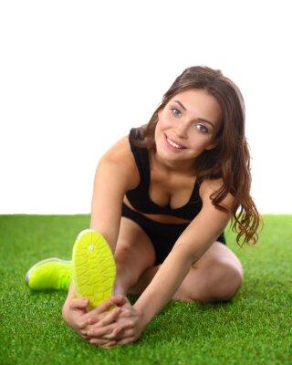 Plakat Kobieta robi ćwiczenia rozciągające na zielonej trawie
