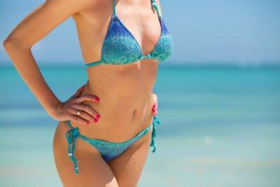 Plakat Kobieta w bikini stwarzających na plaży