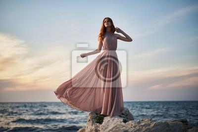 Plakat kobieta w długiej różowej sukience na plaży, zachód słońca