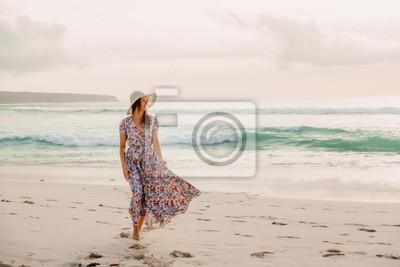 Plakat Kobieta w letniej sukience na plaży o zachodzie słońca lub wschodzie słońca. Kobieta i ocean