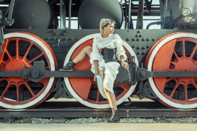 Plakat Kobieta w zabytkowe Sukienka siedzi na koła lokomotywy.