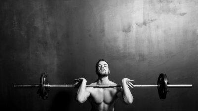 Plakat Kulturystyka, Młody Athletic Strong Man Podnoszenie ciężarów, czarno-biały w studio
