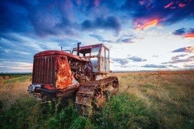 Plakat ld zardzewiały traktor w polu o zachodzie słońca