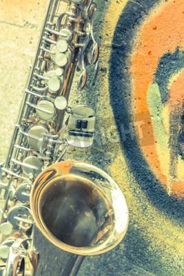 Plakat Lone stary saksofon pochyla się przed murem poza opuszczonym klubie jazzowym