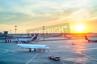 Plakat Lotnisko z wieloma samolotami w piękny zachód słońca