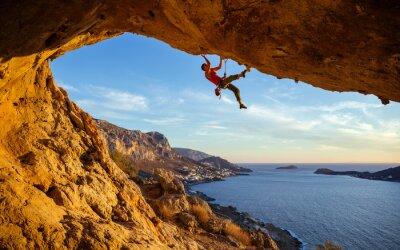 Plakat Mężczyzna Climber na Rock Against pięknym widokiem na wybrzeżu poniżej