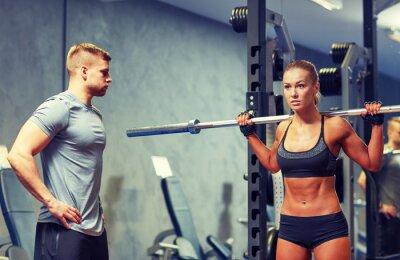 Plakat Mężczyzna i kobieta z sztangą wyginanie mięśni w siłowni