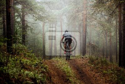 Plakat mężczyzna sportowiec mountainbiker jeździ na rowerze szlakiem leśnym. mgłą lesie, tajemniczy widok