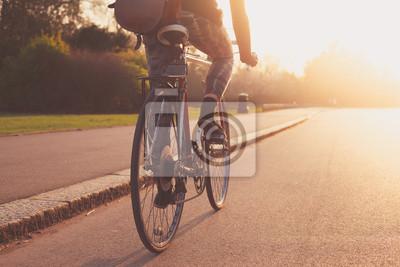Plakat Młoda kobieta na rowerze w parku przy zachodzie słońca