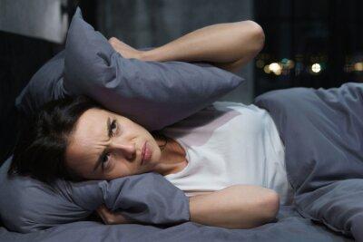 Plakat Młoda kobieta próbuje zasnąć, ale przeszkadzają jej głośni sąsiedzi i zakrywa uszy poduszkami