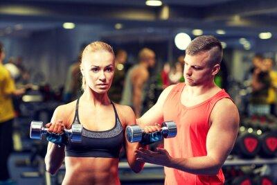Plakat młoda para z mięśni w siłowni hantle wyginanie