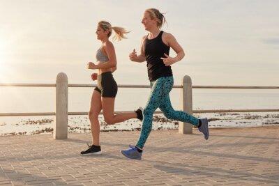 Plakat Młode kobiety biegnące wzdłuż nadmorskiej promenady