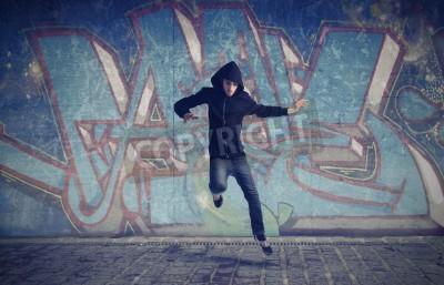 Plakat Młody człowiek skacząc z graffiti w tle