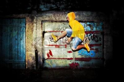 Plakat Młody człowiek skoków / taniec na tle ściany graffiti, grunge