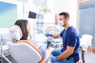 Plakat Młody dentysta taktuje żeńskiego pacjenta w stomatologicznym studiu