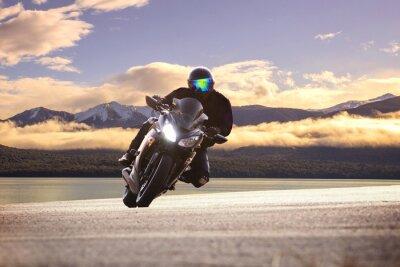 Plakat Młody mężczyzna jedzie duży rower motocykl przed ostrym łuku ASPH