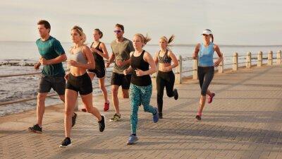 Plakat Młodzi ludzie biegnące wzdłuż plaży promenady
