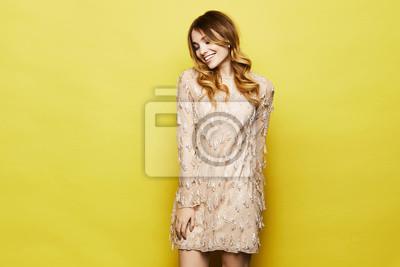 Plakat Modna i emocjonalna blondynka modela dziewczyna z jaskrawym makeup z błyszczącym uśmiechem w eleganckiej brzoskwini sukni pozuje w studiu przy żółtym tłem ,.