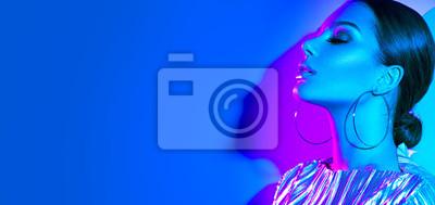 Plakat Mody modela brunetki kobieta w kolorowych jaskrawych neonowych światłach pozuje w studiu. Piękna seksowna dziewczyna, modny świecący makijaż, metalowe srebrne usta