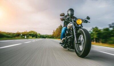 Plakat motocykl na drodze. dobrze się bawiąc pustą drogą podczas wycieczki / podróży motocyklem