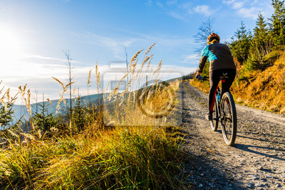 Plakat Mountain biking woman riding on bike in summer mountains forest landscape. Woman cycling MTB flow trail track. Outdoor sport activity.