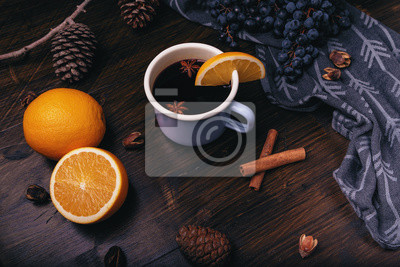 Plakat Mulled wine with spices, grapes, pine cones, cinnamon and oranges on a dark wooden background