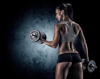 Plakat Muskularna kobieta w studio na ciemnym tle