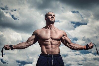 Plakat Muskularny mężczyzna pod pochmurne niebo