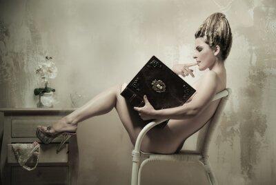 Plakat Naga kobieta siedzi w fotelu czyta książkę w domu