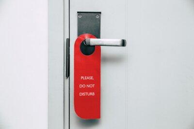 Plakat Nie przeszkadzaj czerwoną wiszącą etykietą na klamce drzwi pokoju hotelowego