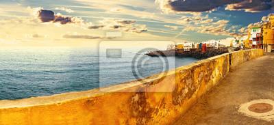 Paisaje de mar y pueblo costero.Casas sobre el acantilado y puesta de sol.Puerto de la cruz, Teneryfa, Islas Canarias