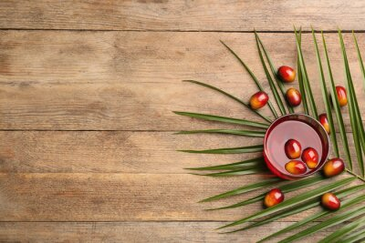 Plakat Palm oil in glass with fruits and tropical leaf on wooden table, flat lay. Space for text