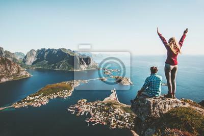 Plakat Para rodzina podróżujących razem na krawędzi klifu w Norwegii koncepcja życia mężczyzny i kobiety letnie wakacje odkryty widok z lotu ptaka Lofoten wyspy Reinebringen góra góry