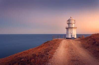 Plakat Piękna biała latarnia na wybrzeżu oceanu o zachodzie słońca. Lan