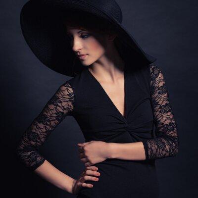 Plakat piękna dziewczyna w czarnej sukni i kapeluszu