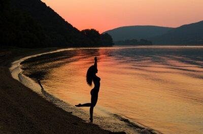 Plakat Piękna i seksowna kobieta, długie włosy na plaży o zachodzie słońca