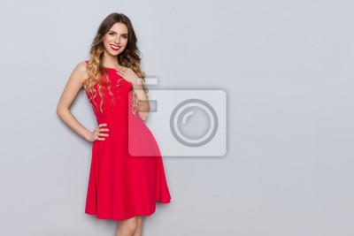 Plakat Piękna kobieta w czerwonej sukience trzyma rękę na klatce piersiowej i uśmiecha się