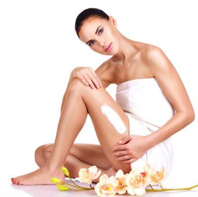 Plakat Piękna młoda kobieta przy użyciu kremu.