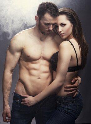 Plakat Piękna młoda uśmiechnięta para w miłości obejmującego kryty