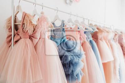 Plakat Piękne eleganckie bujne różowe i niebieskie sukienki dla dziewczynek na wieszakach na tle białej ściany. Sukienki dziecięce z piórami na bal i święto.
